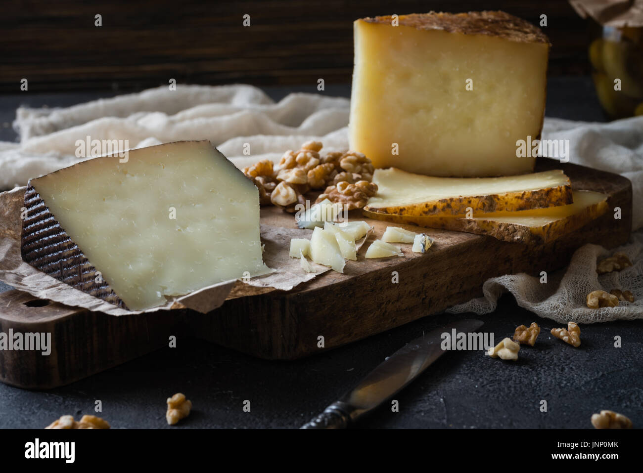 Cheese platter of chopped Spanish hard cheese manchego and sliced Italian pecorino toscano) on wooden board, with green olives in glass jar and walnut - Stock Image