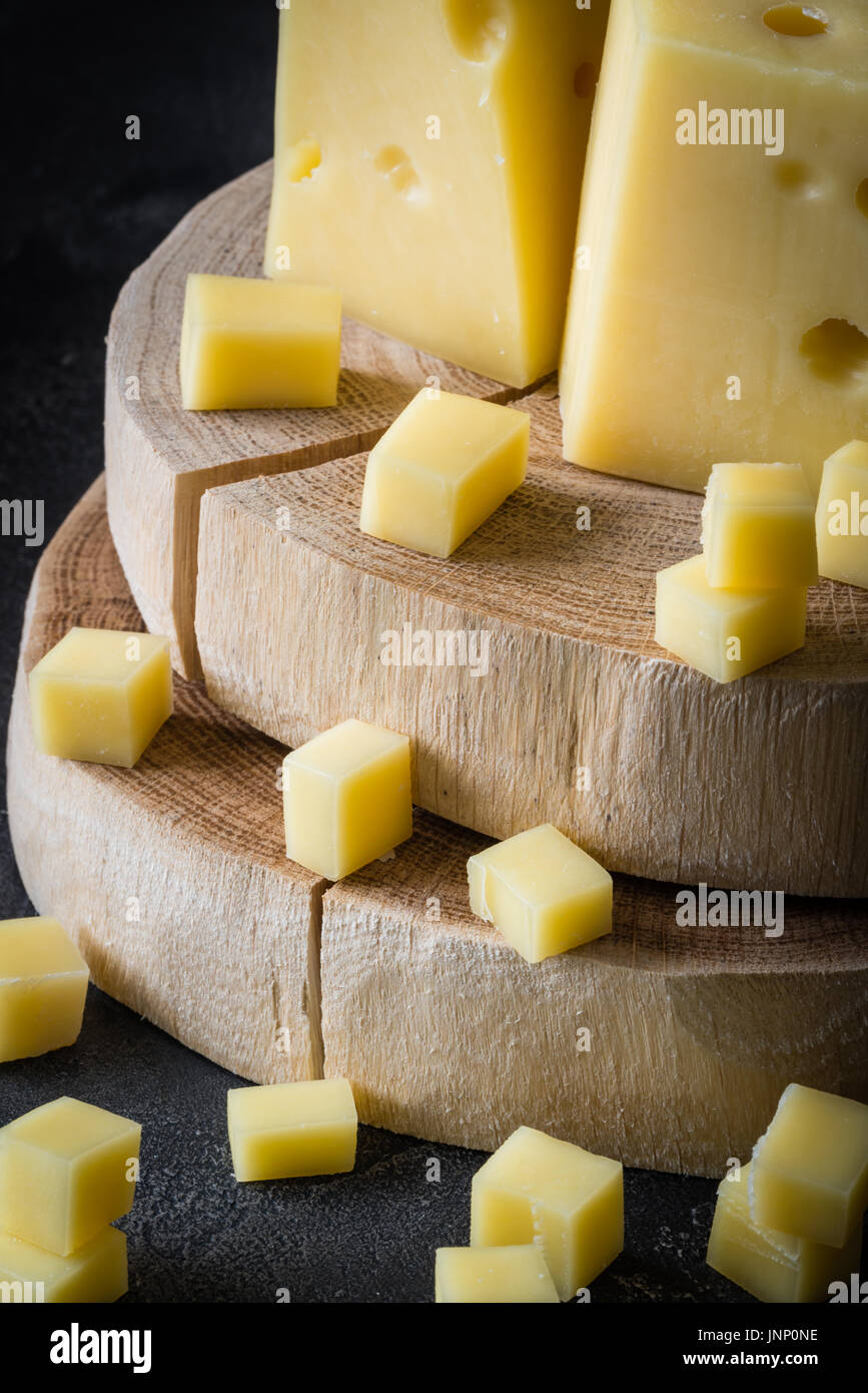 Close up of Swedish hard yellow cheese with holes chopped on wooden slices on dark rustic background - Stock Image