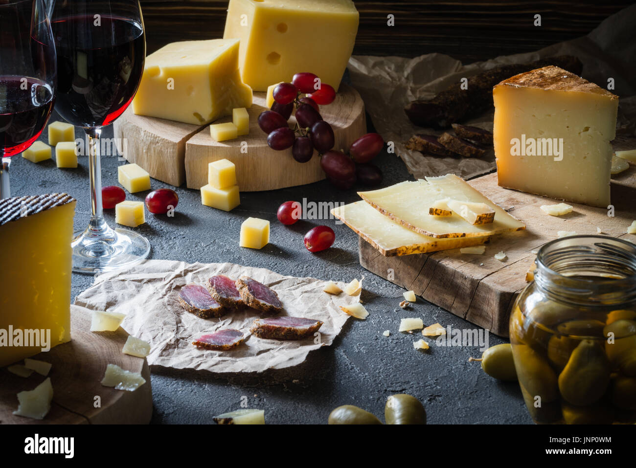 Cheese platter of chopped hard cheeses (Swedish, Spanish manchego) and sliced Italian pecorino toscano on wooden boards, with green olives in glass ja - Stock Image