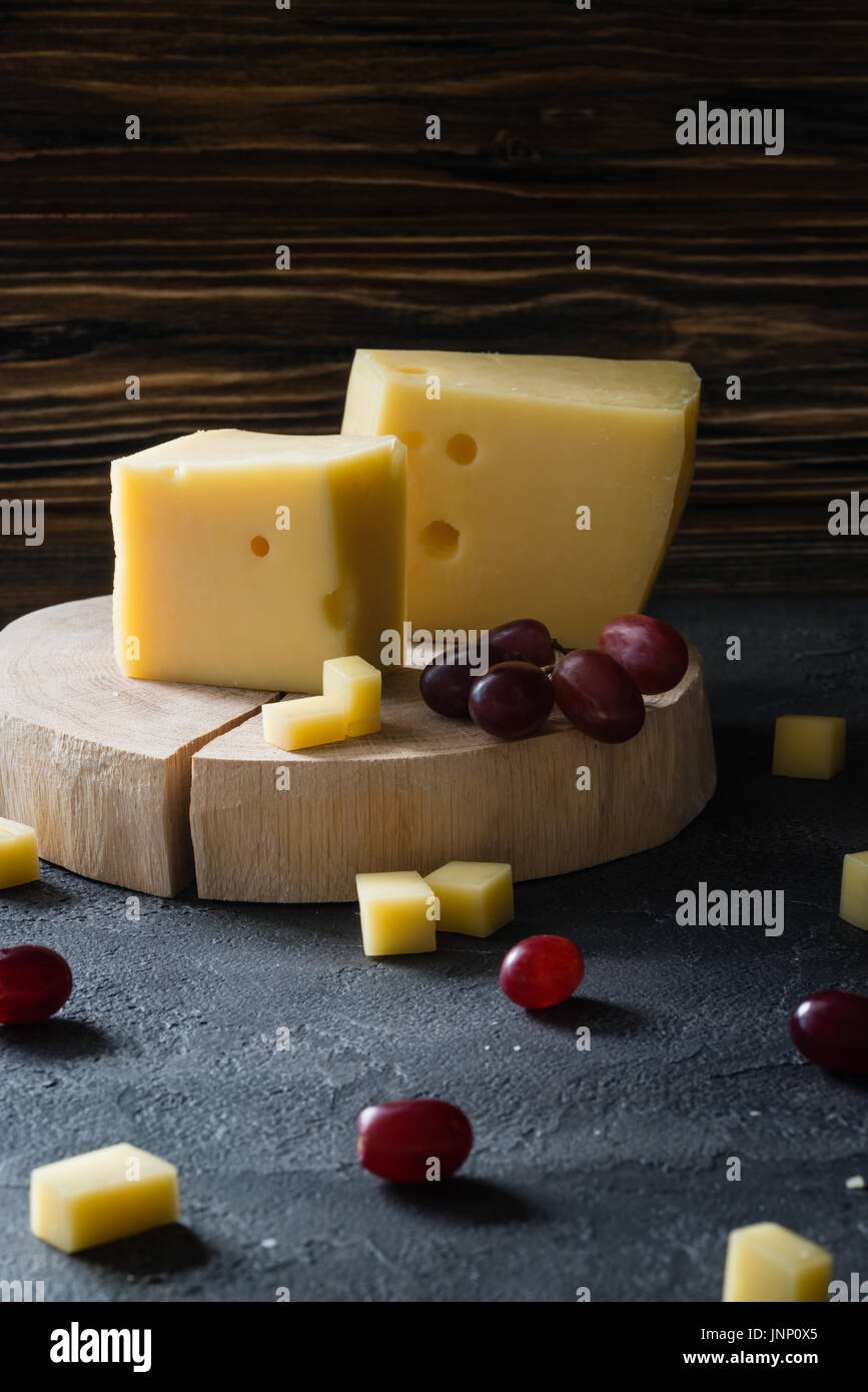 Swedish hard yellow cheese with holes chopped with red grapes on wooden slices on dark rustic background - Stock Image