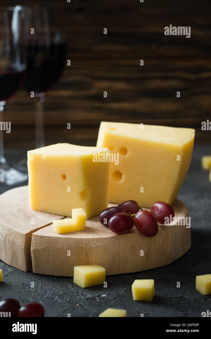 Swedish hard yellow cheese with holes chopped with red grapes on wooden slices and glasses with red wine on dark rustic background - Stock Image
