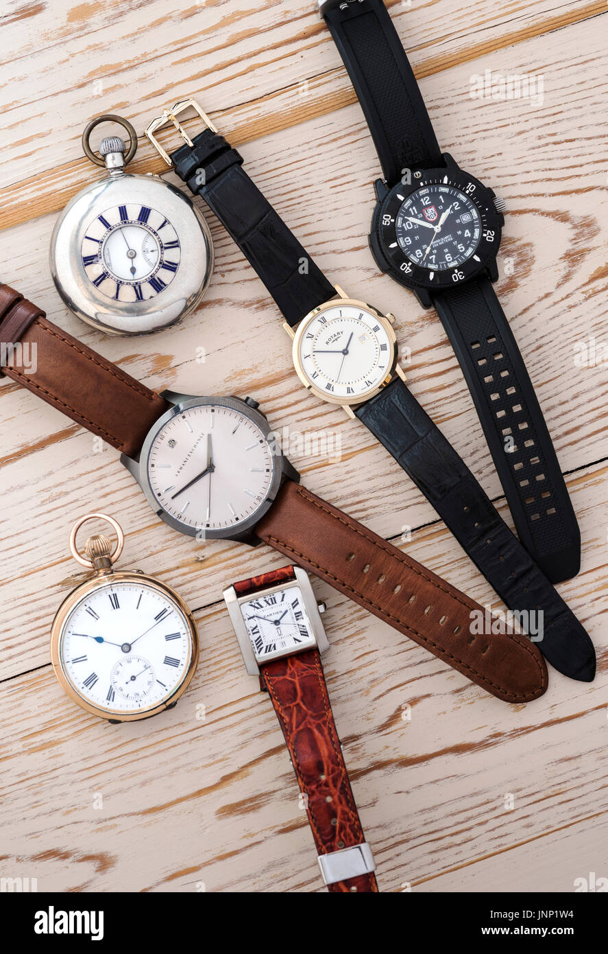 Group of four mens wristwatches, and two pocket watches on a wooden background. - Stock Image