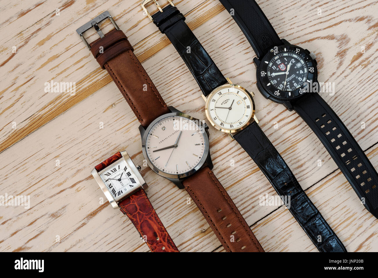 Group of four mens wristwatches, on a wooden background. - Stock Image