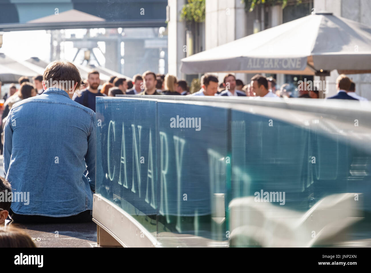 London, UK - May 10, 2017 - Canary Wharf sign with a crowd of people drinking at a dockside bar in the background Stock Photo