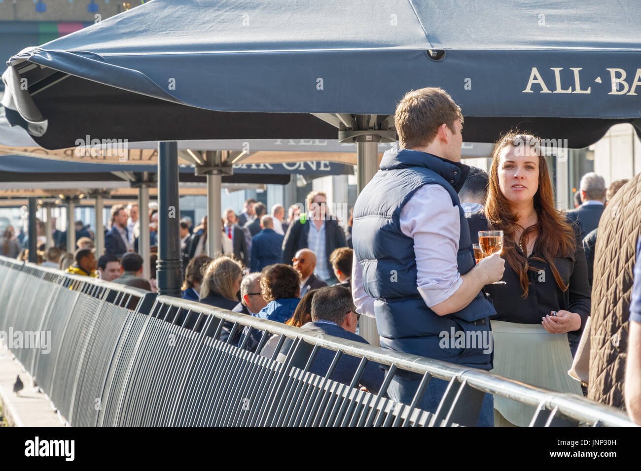 London, UK - May 10, 2017 - A young businesswoman with her colleagues at a dockside bar in Canary Wharf packed with people drinking on a sunny day - Stock Image