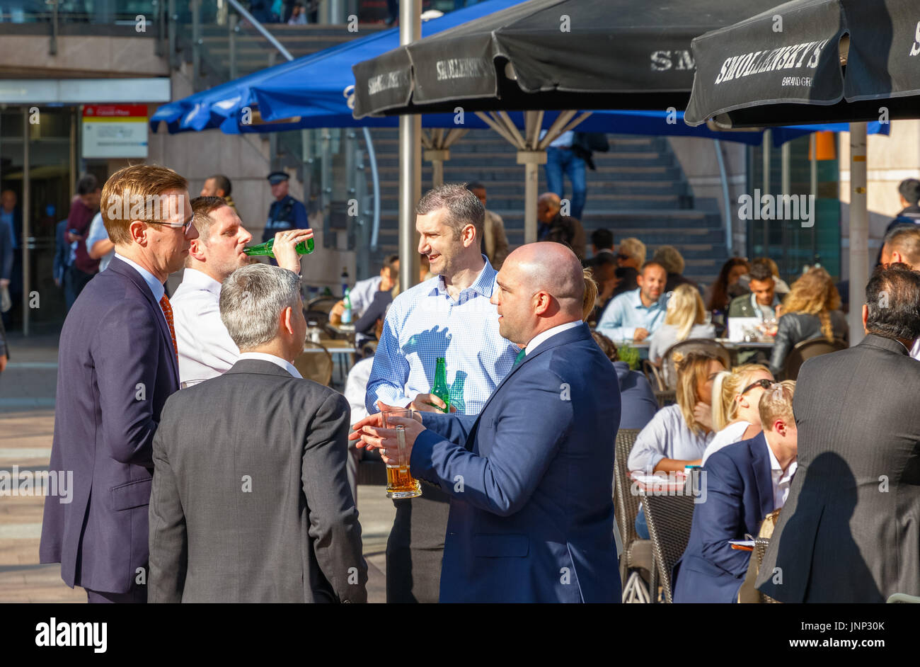 London, UK - May 10, 2017 - Group of businessmen drinking at a outdoor bar in Canary Wharf - Stock Image