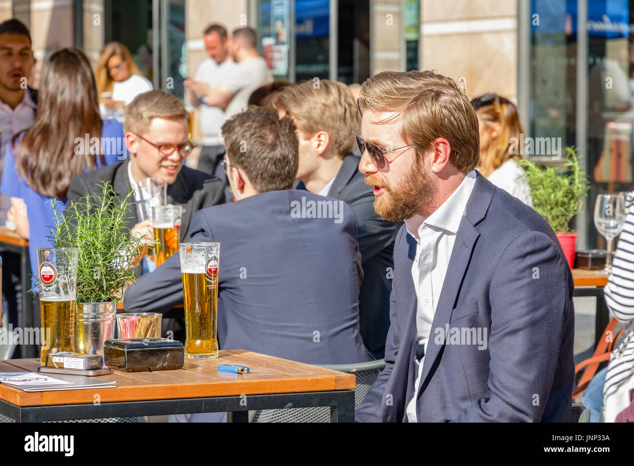 London, UK - May 10, 2017 - A young businessman at a outdoor bar in Canary Wharf packed with people drinking on a sunny day - Stock Image