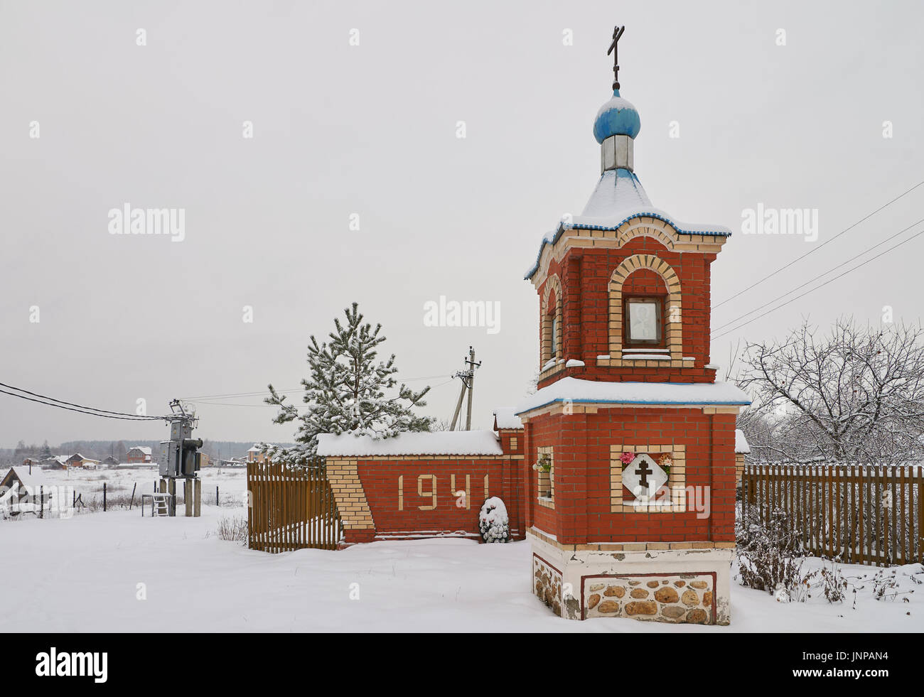 Winter view of red brick chapel and monument to soviet warriors who died in Second World War. Ignatovo village, Stock Photo