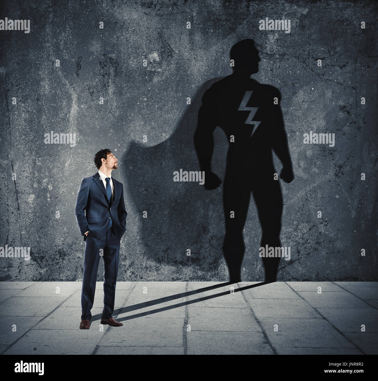 Businessman with his shadow of super hero on the wall. Concept of powerful man - Stock Image