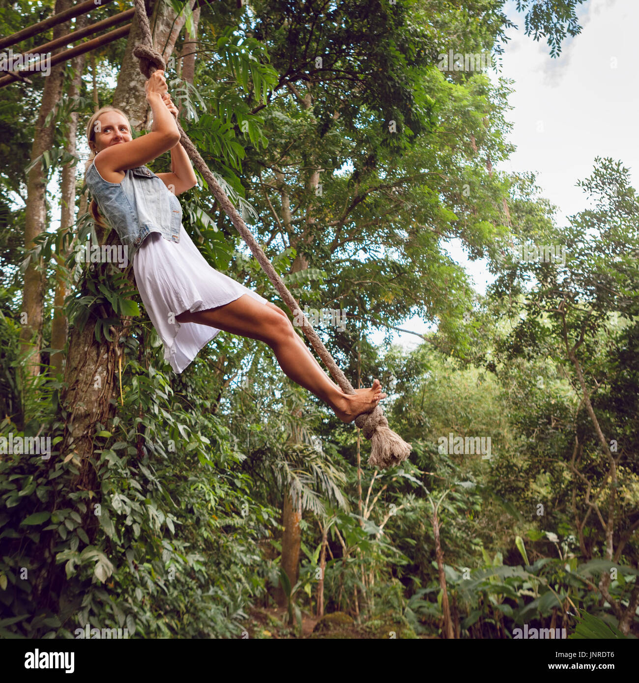 Family travel lifestyle. Happy young woman flying high with fun on rope swing on wild jungle background. Funny adventure Stock Photo