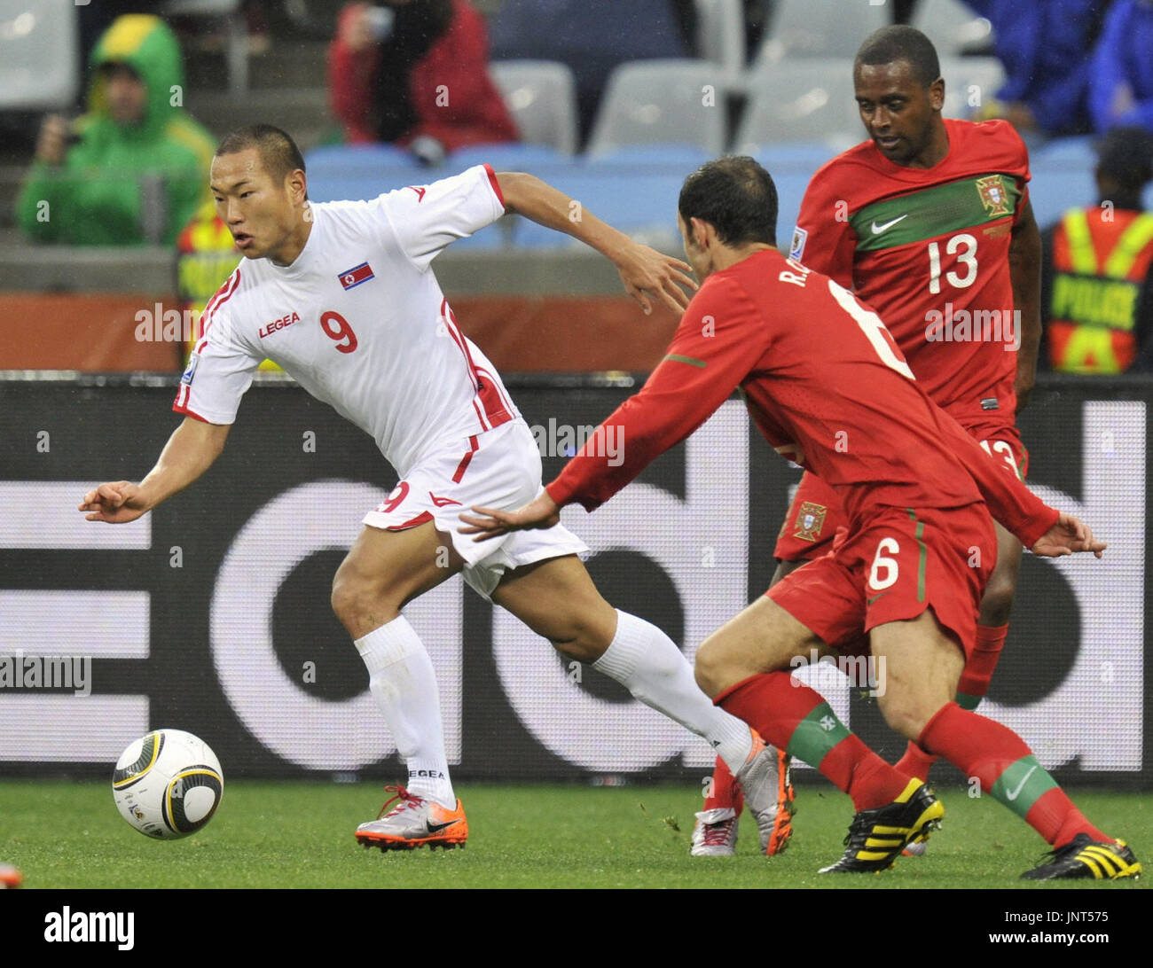 CAPE TOWN, South Africa - North Korea striker Jong Tae Se (L) runs past Portugal's Ricardo Carvalho (6) and Miguel (13) during the first half of a World Cup Group G match at Green Point Stadium in Cape Town on June 21, 2010. (Kyodo) Stock Photo