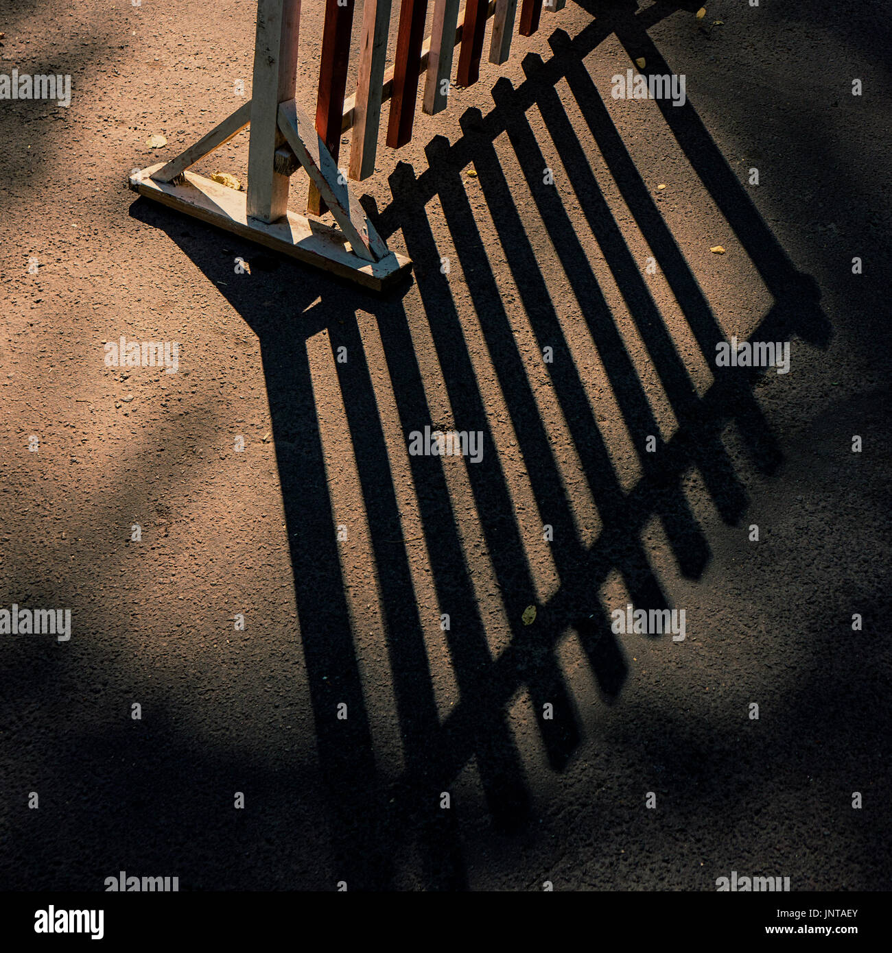 Wooden fence and contrasting shadow on the ground - Stock Image