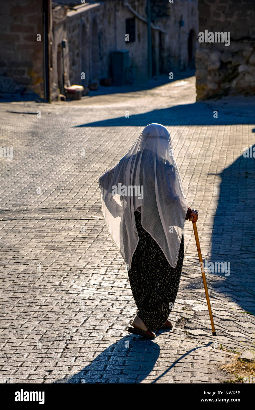 Elderly woman walking the streets of Goreme in Cappadocia with Muslim veil - Stock Image