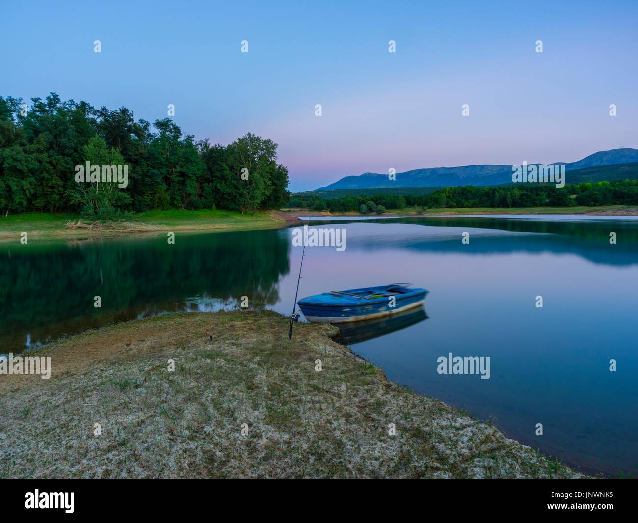 Peruca lake in Croatia fishing stick wooden boat dusk evening time calm calmness Stock Photo