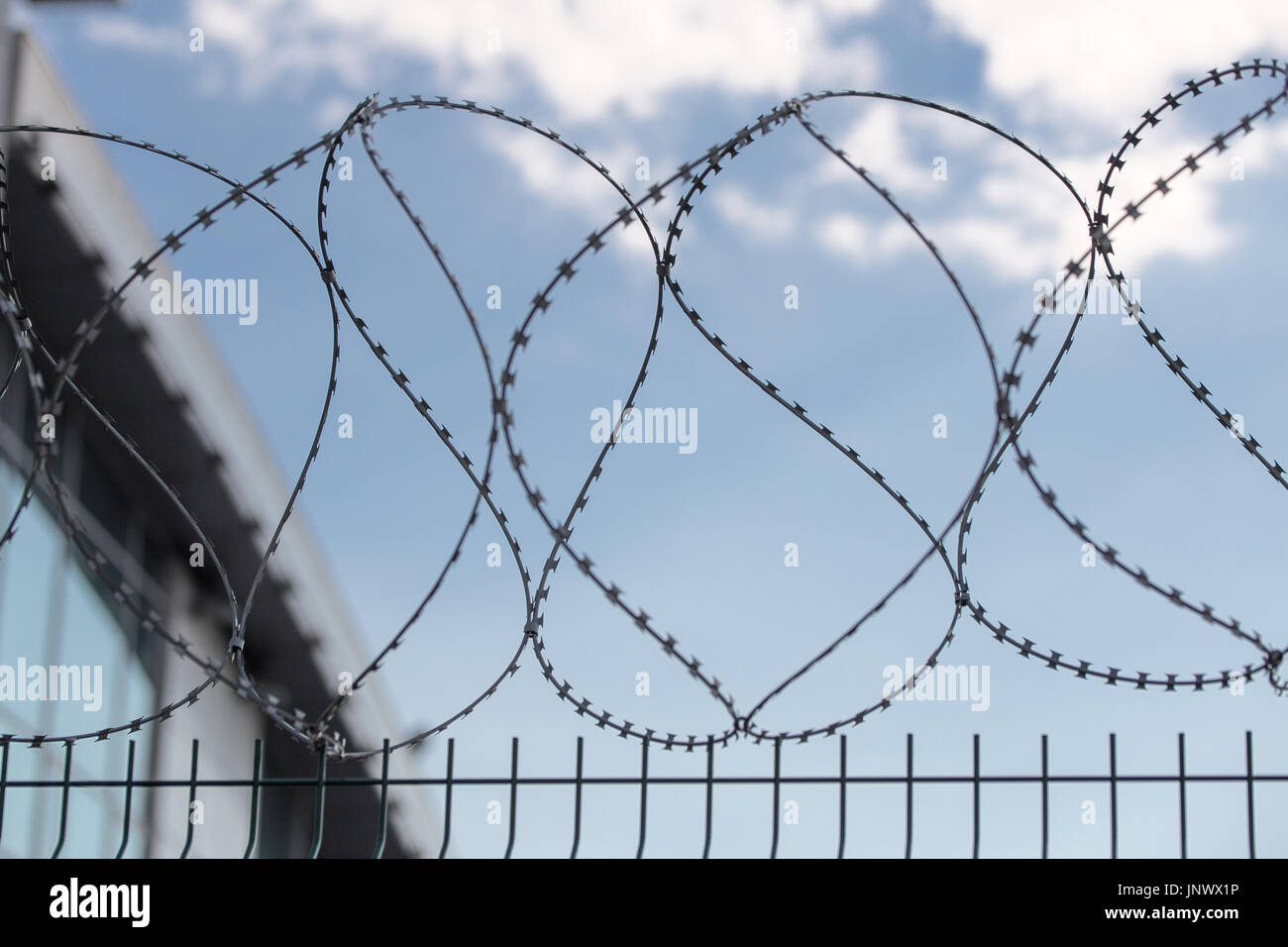 Safe protective metal fence with barbed wire. Corner of a protected building and blue sky with clouds on the background. Secured area. - Stock Image