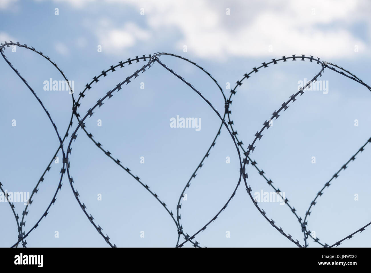 Safe protective metal fence with barbed wire and blue sky with clouds on the background. Secured area. - Stock Image