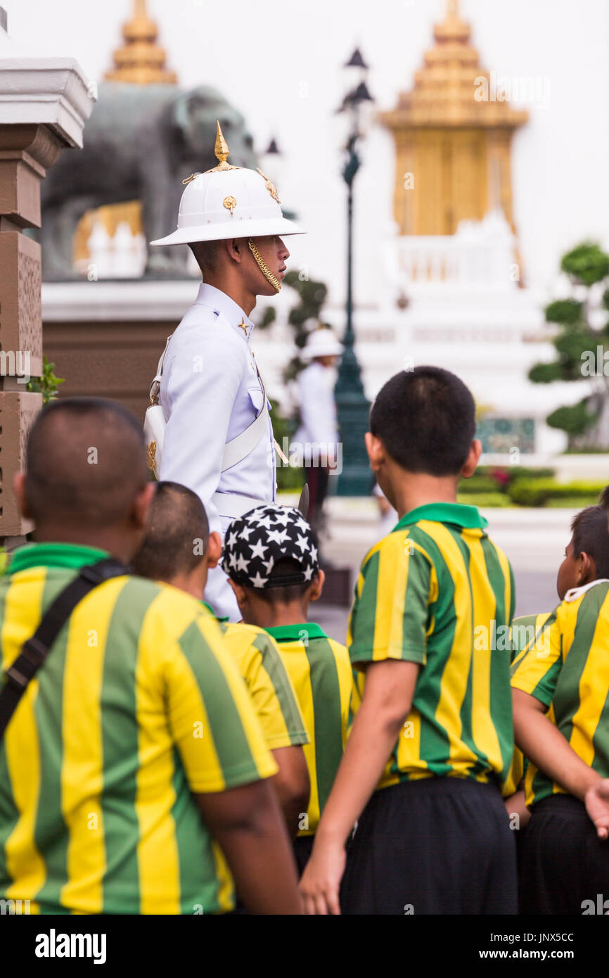 Bangkok, Thailand - February 18, 2015: Group of schoolchildren in yellow and green striped uniform visiting the Grand Palace in Bangkok. - Stock Image