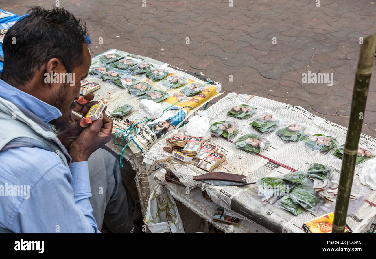 Street seller of betel nut leaves and areca for chewing while lighting a cigarette, Shillong, Meghalaya, India - Stock Image