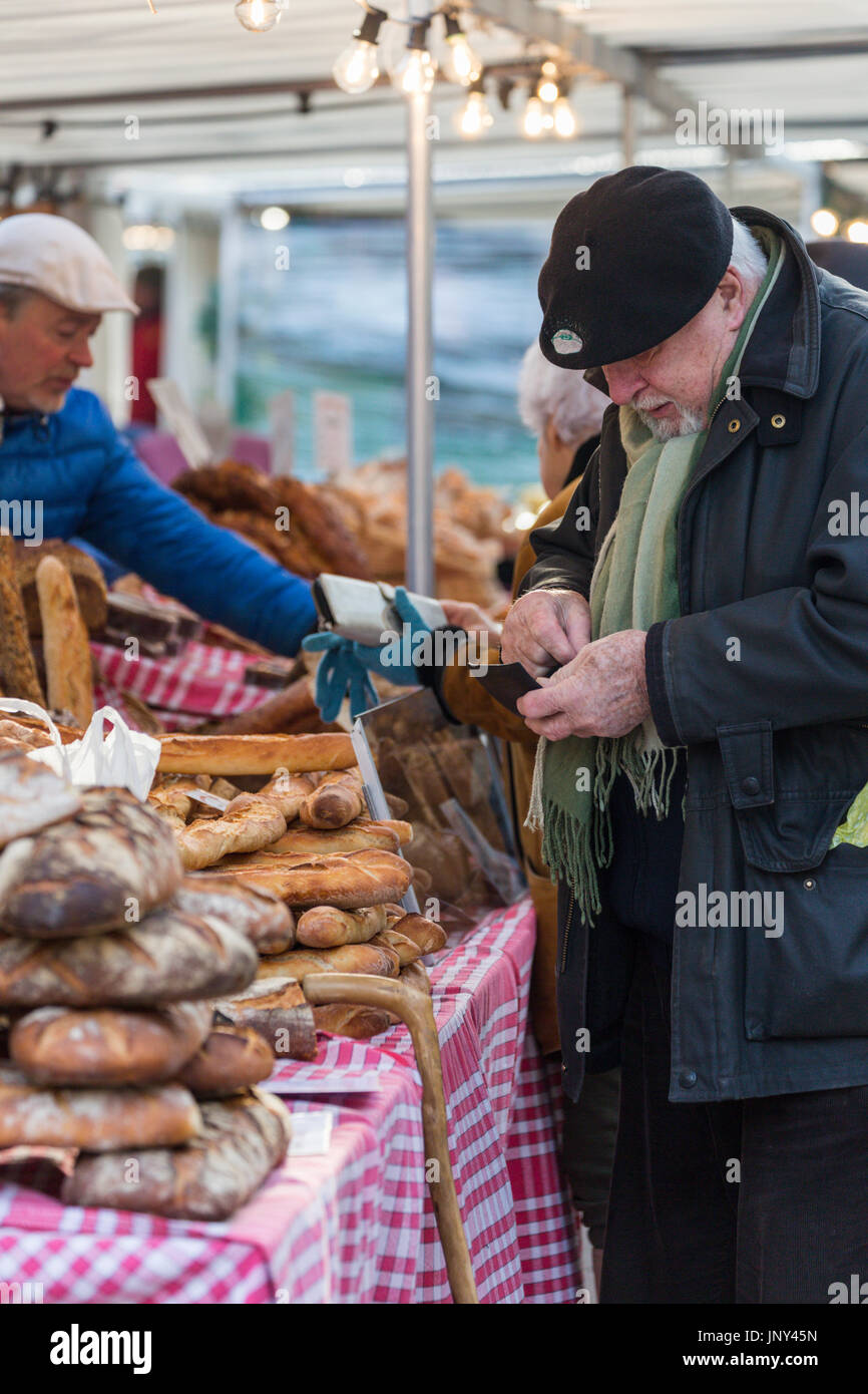 Paris. France - February 27, 2016: Older Frenchman in beret buying bread at the Saxe-Breteuil market in the 7th arrondissement of Paris. - Stock Image
