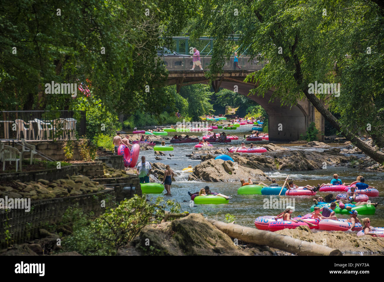 Families and friends tubing through downtown Helen, Georgia on the Chattahoochee River in the Blue Ridge Mountains. - Stock Image