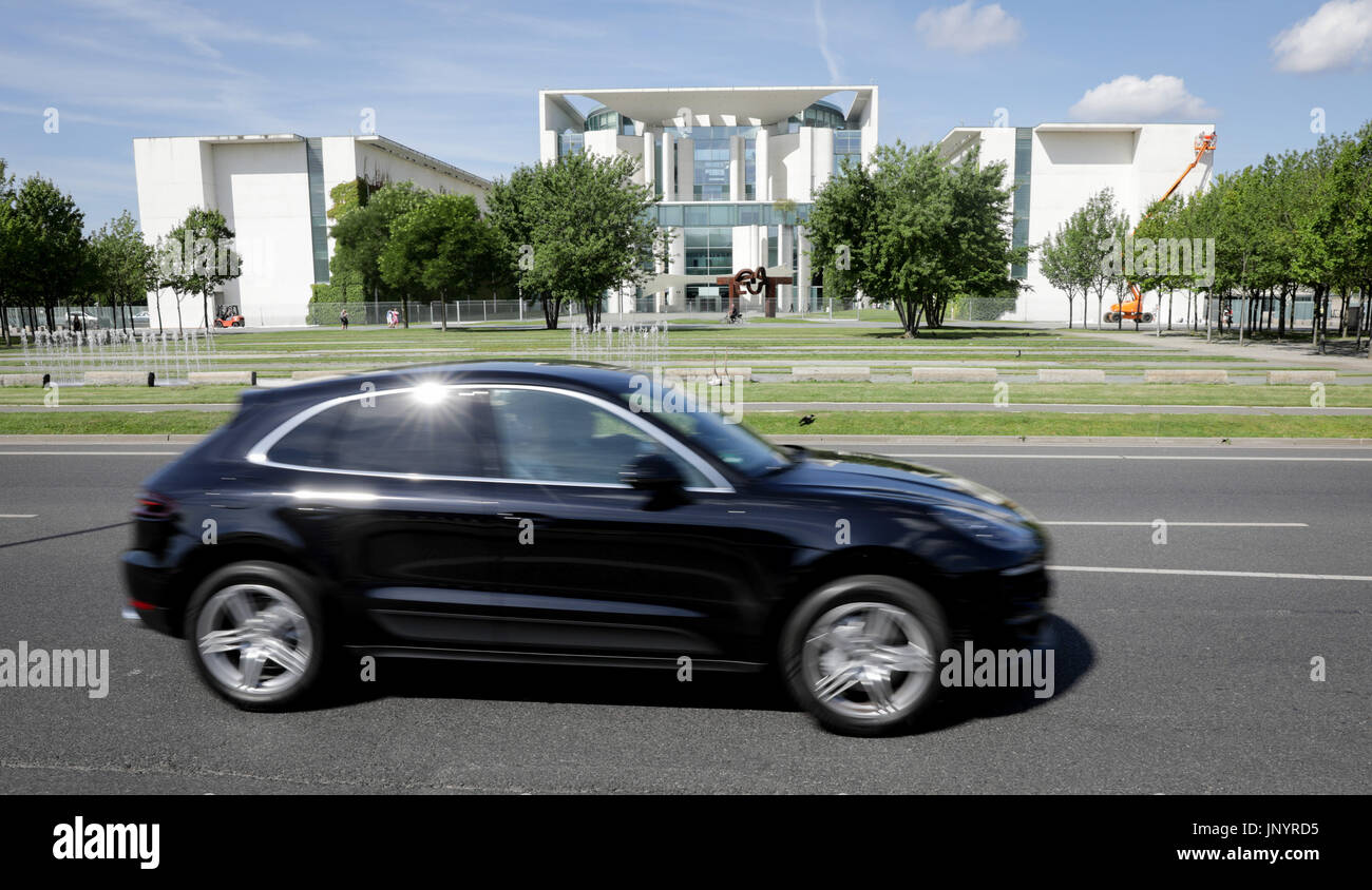 Berlin, Germany. 31st July, 2017. A Porsche Macan drives by the Federal Chancellery in Berlin, Germany, 31 July 2017. On Wednesday, the federal government and the automotive industry want to meet during a 'Diesel Summit' in order to discuss the consequences of the emmissions scandal and the suspicions of a cartel of the producers. Photo: Kay Nietfeld/dpa/Alamy Live News - Stock Image