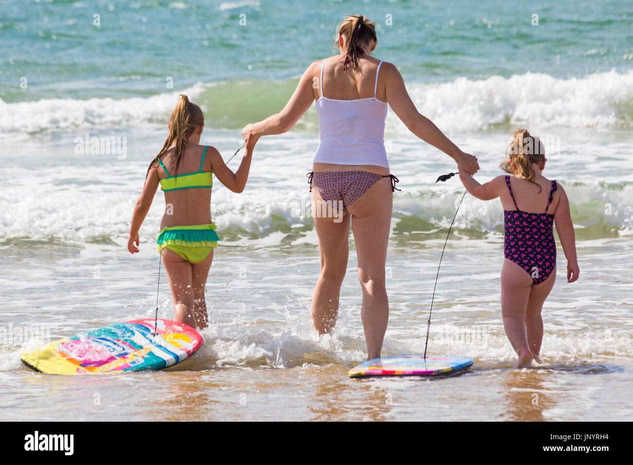 Bournemouth, Dorset, UK. 31st July, 2017. UK weather: after a weekend of mixed weather, a warm sunny start to the new week, as visitors head to the seaside to make the most of the sunshine. Mia, aged 6, and Bella, aged 4, enjoy playing in the sea with their body boards. Credit: Carolyn Jenkins/Alamy Live News - Stock Image