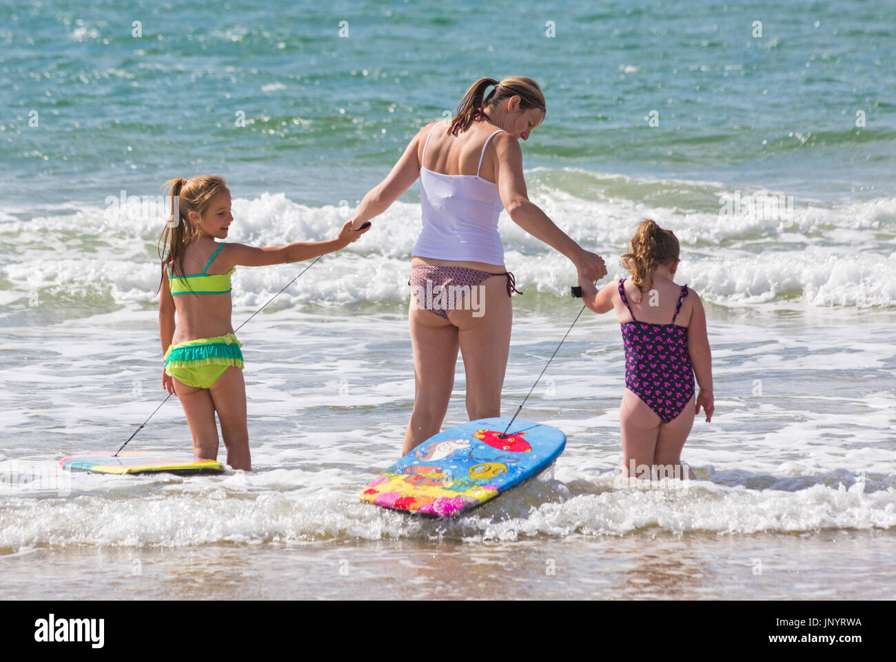 Bournemouth, Dorset, UK. 31st July, 2017. UK weather: after a weekend of mixed weather, a warm sunny start to the new week, as visitors head to the seaside to make the most of the sunshine. Mia, aged 6, and Bella, aged 4, enjoy playing with their body boards in the sea. Credit: Carolyn Jenkins/Alamy Live News - Stock Image