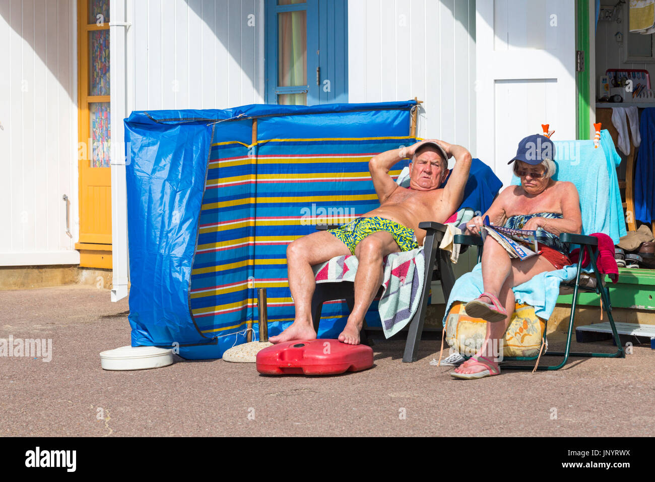 Bournemouth, Dorset, UK. 31st July, 2017. UK weather: after a weekend of mixed weather, a warm sunny start to the new week, as visitors head to the seaside to make the most of the sunshine. Mature couple relaxing in the sun at beach hut. Credit: Carolyn Jenkins/Alamy Live News - Stock Image