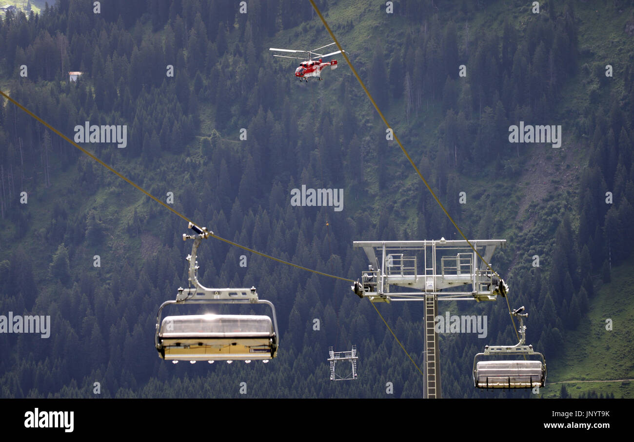 Riezlern, Austria. 31st July, 2017. A transport helicpoter Kamov KA 32 A12 transports a part of a cable car support up the Ifen in the Kleinwalser valley near Riezlern, Austria, 31 July 2017. The helicporter flies across an already finished section of the cable car. 18 of the extremy heavy supports are currently being mounted in 60 flights at the Ifen. The 2230-metre-high mountain is located at the border between Germany and Austria. Photo: Karl-Josef Hildenbrand/dpa/Alamy Live News - Stock Image