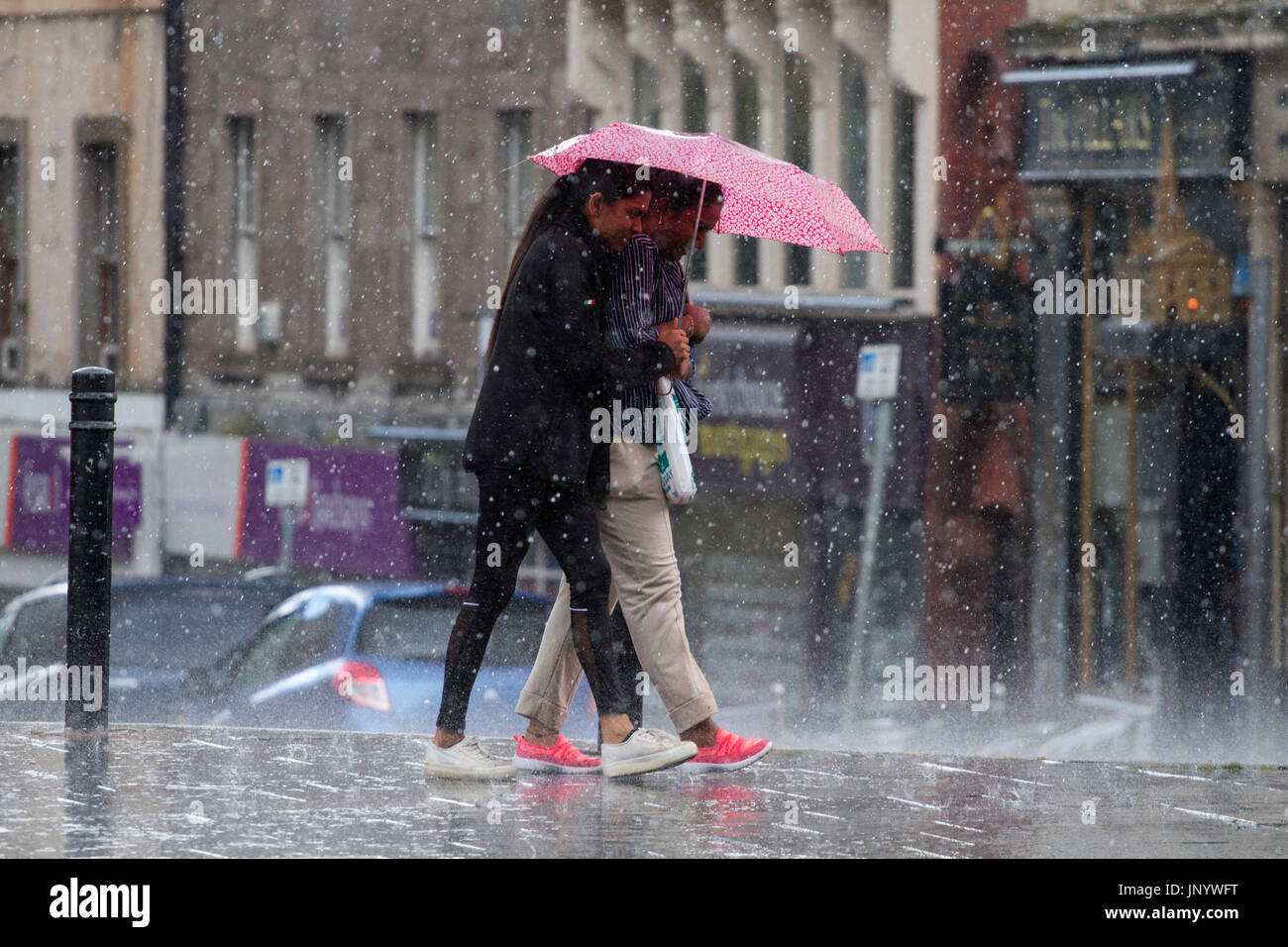 Dundee, Tayside, Scotland. 31st July, 2017. UK Weather: Torrential heavy downpours of rain soak shoppers in Dundee City Centre. The unsettled weather across Tayside caught shoppers by surprise with heavy outbursts of rain during the day. Some were prepared but others use alternative ways to shelter. Credit: Dundee Photographics /Alamy Live News Stock Photo