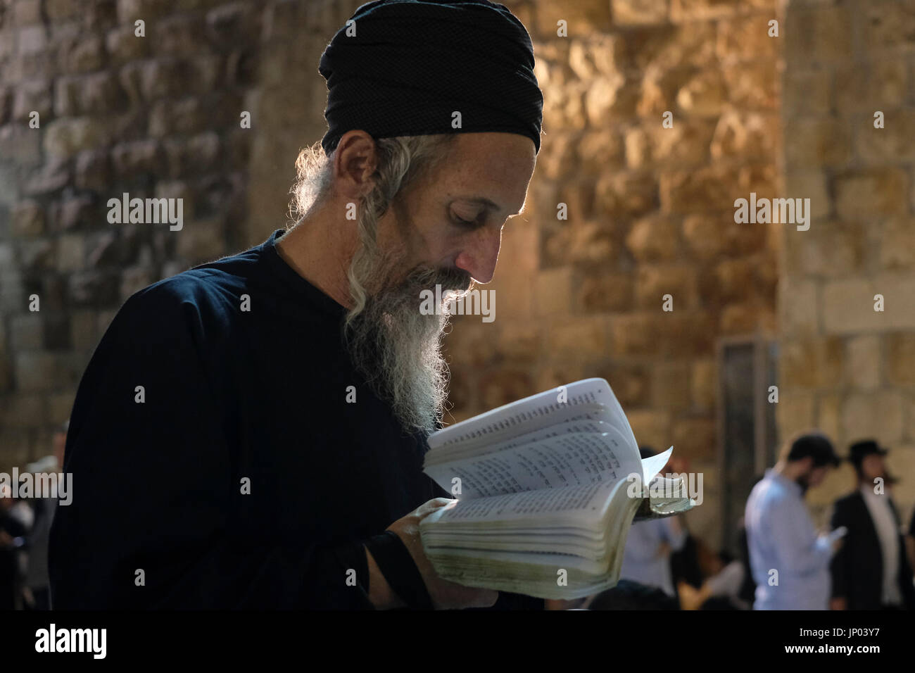 Israel, Jerusalem 31st July. Orthodox Jewish man mourning and reading from the biblical Book of Lamentation on Tisha B'Av feast at the Western Wall in Jerusalem Israel on 31 July 2017. Tisha B'Av is an annual fast day in Judaism, The fast commemorates the destruction of the First and Second Temples in Jerusalem, which occurred about 656 years apart, but on the same date. Accordingly, the day has been called the 'saddest day in Jewish history. - Stock Image