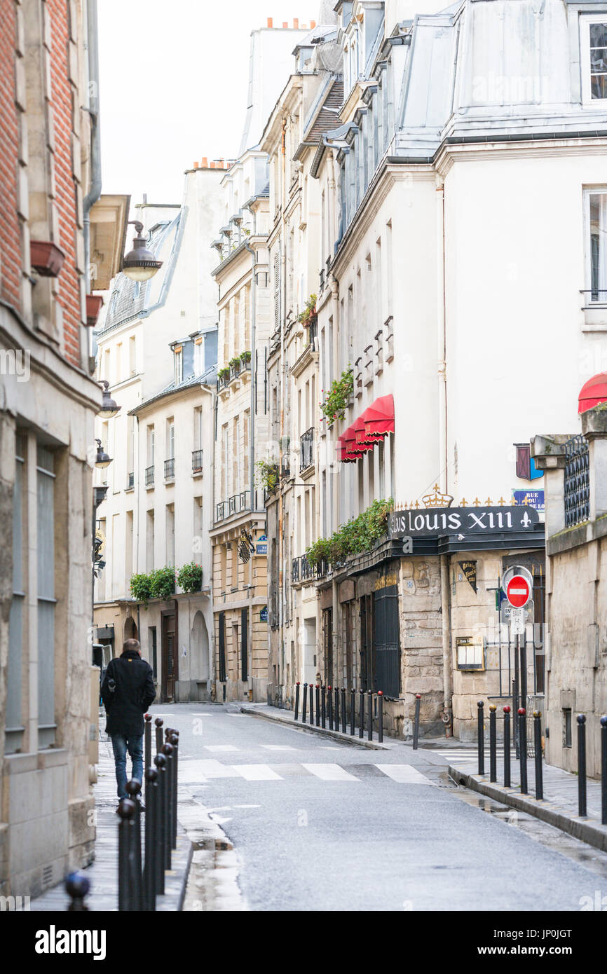 Paris, France - March 2, 2016: Man walking down rue des Grands Augustins in Monnaie on the Left Bank, Paris, France. - Stock Image