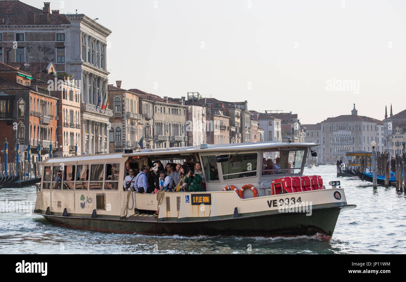 Venice, Italy - April 26, 2012: A vaporetto (water bus) full of passengers on the Grand Canal. The vaporettos are the main form of bulk transport in Venice, going up and down the Grand Canal making frequent stops and also across the lagoon. - Stock Image