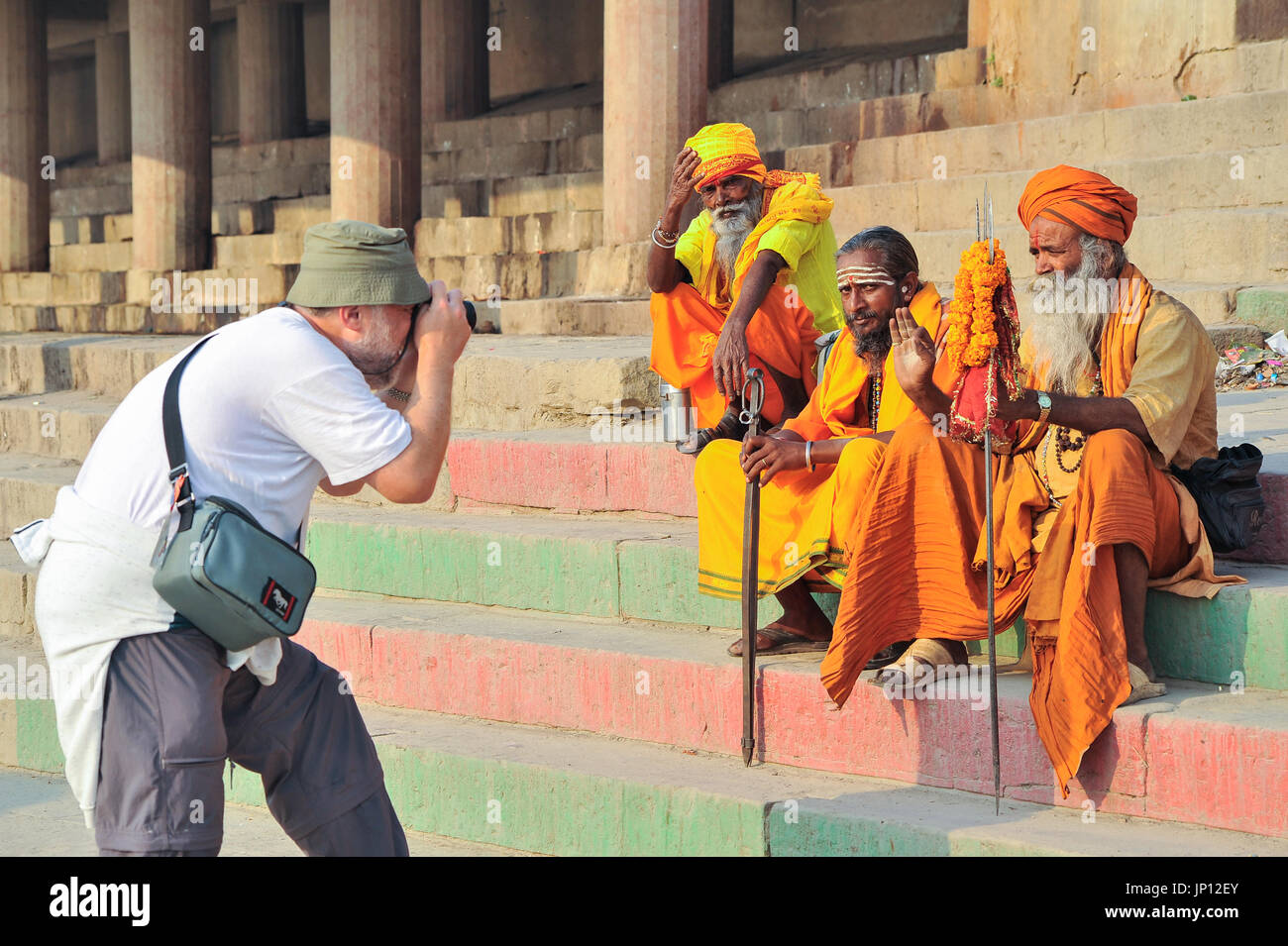 Tourist photographing Sadhus (Holy Men) on the steps of the Ganges in Varanassi - Stock Image
