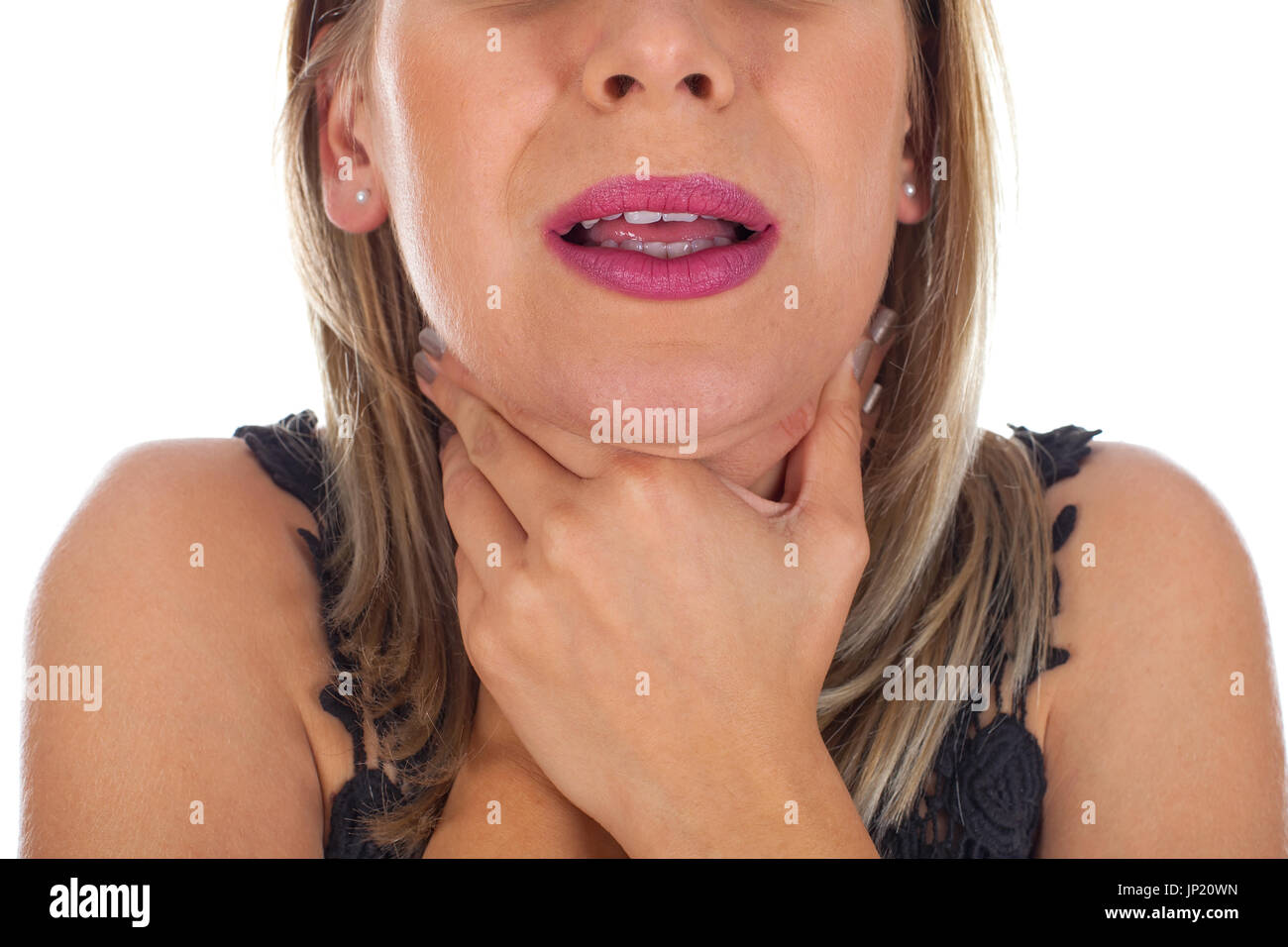 Picture of young woman having sore throat holding her neck, checking the inflamed glands - isolated background - Stock Image