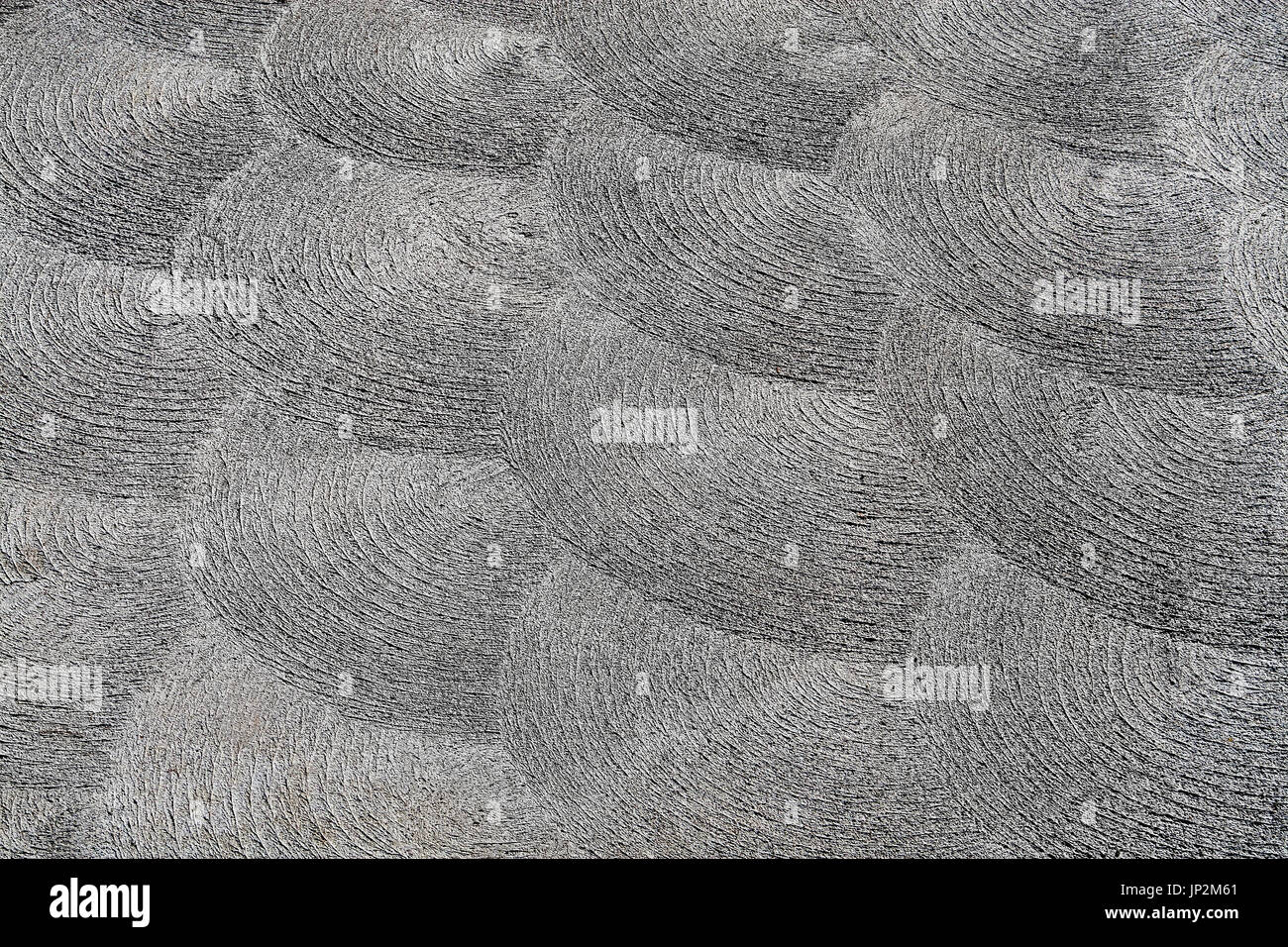 Decorative swirling and grooved monochromatic abstract pattern on sidewalk - Stock Image