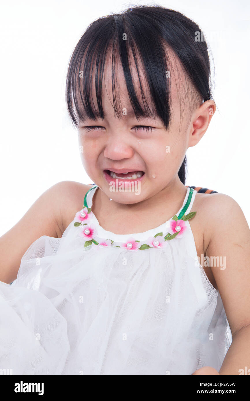 Crying Asian Chinese little girl in isolated white background - Stock Image