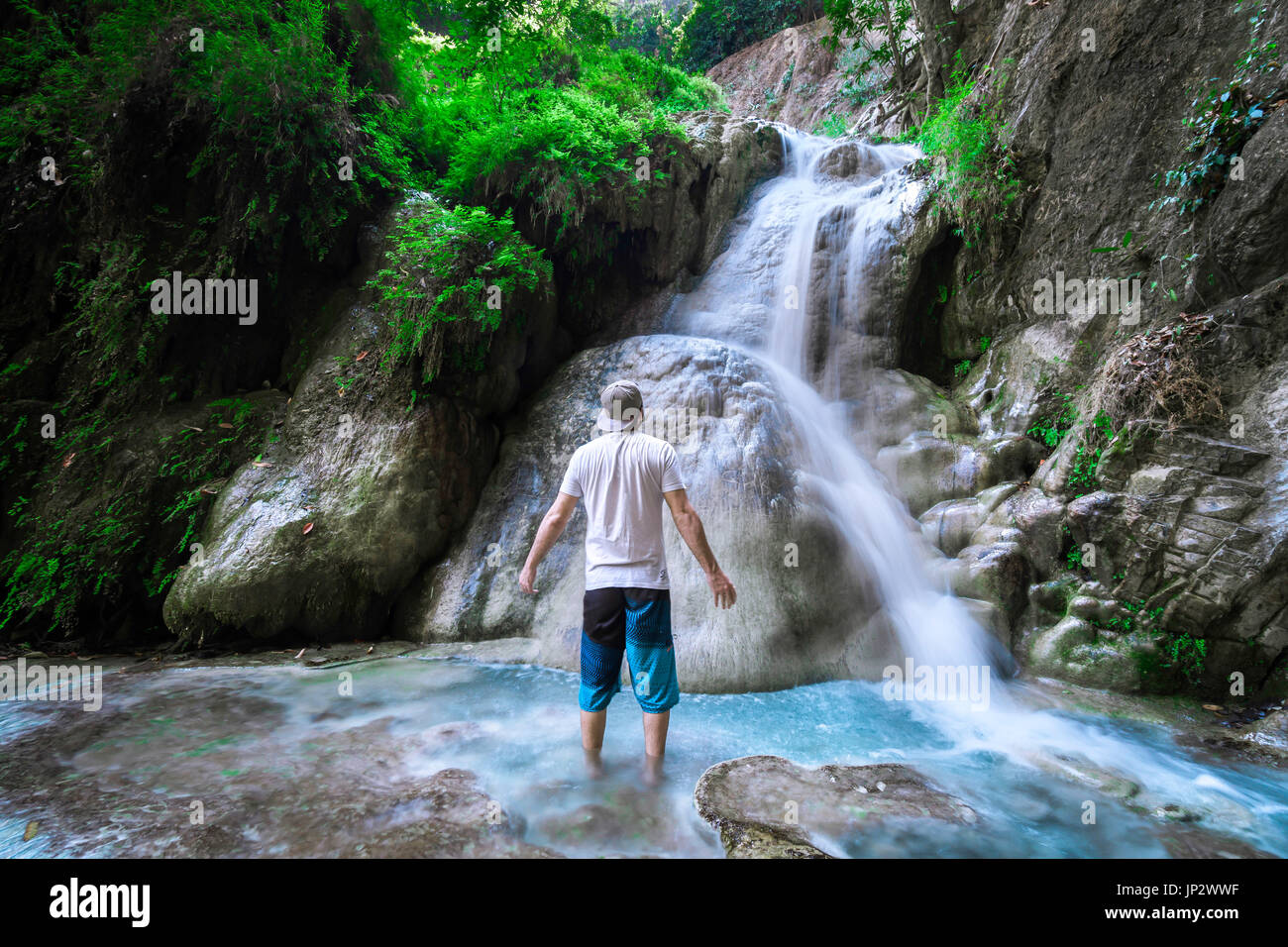 Man Solo traveler standing in front of  a waterfall in the jungle. - Stock Image