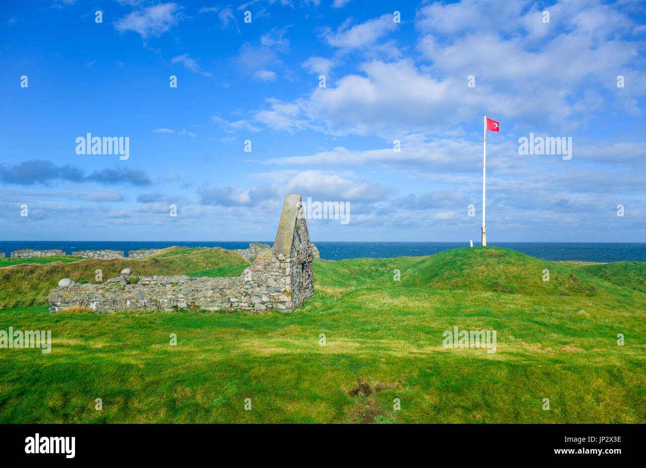 The remains of Peel Castle constructed by vikings on top of Peel hill with Isle of Man national flag on a clear blue sky - Stock Image