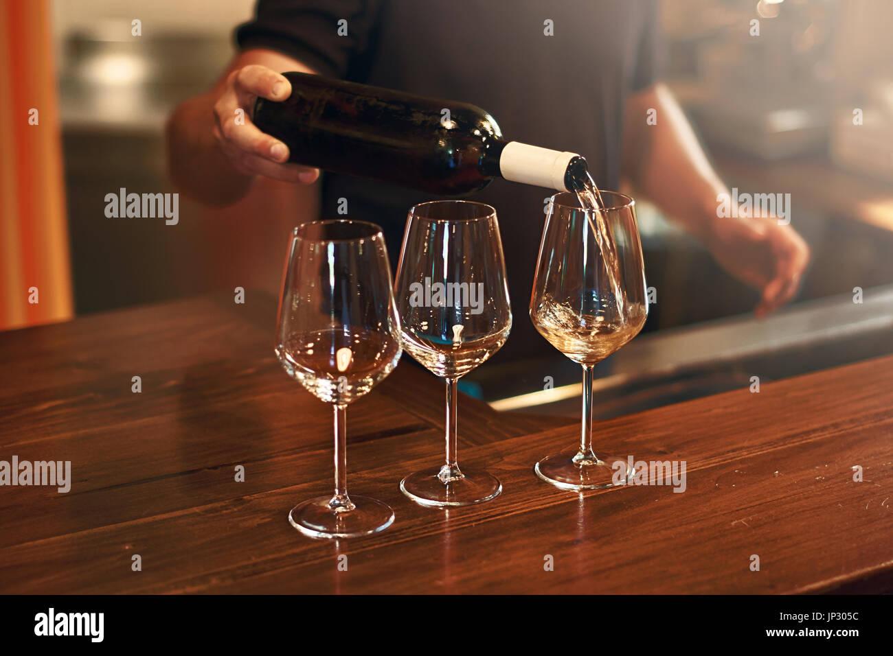 Sommelier pours pinot gris wine in glasses for degustation - Stock Image