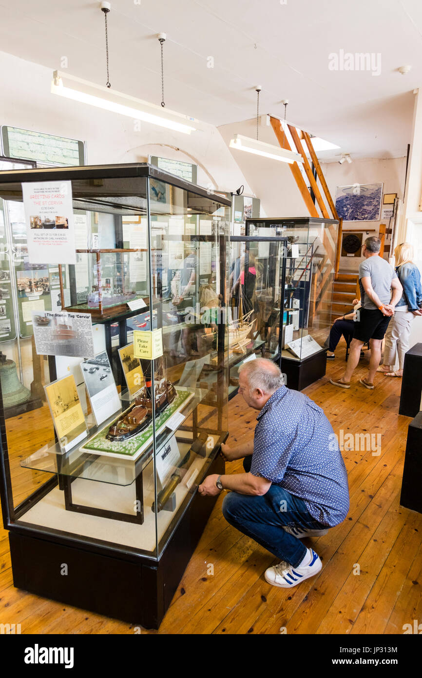 Interior of Ramsgate harbour maritime museum. Dunkirk evacuation display with Caucasian man kneeling down to study one of the displays in glass case. - Stock Image
