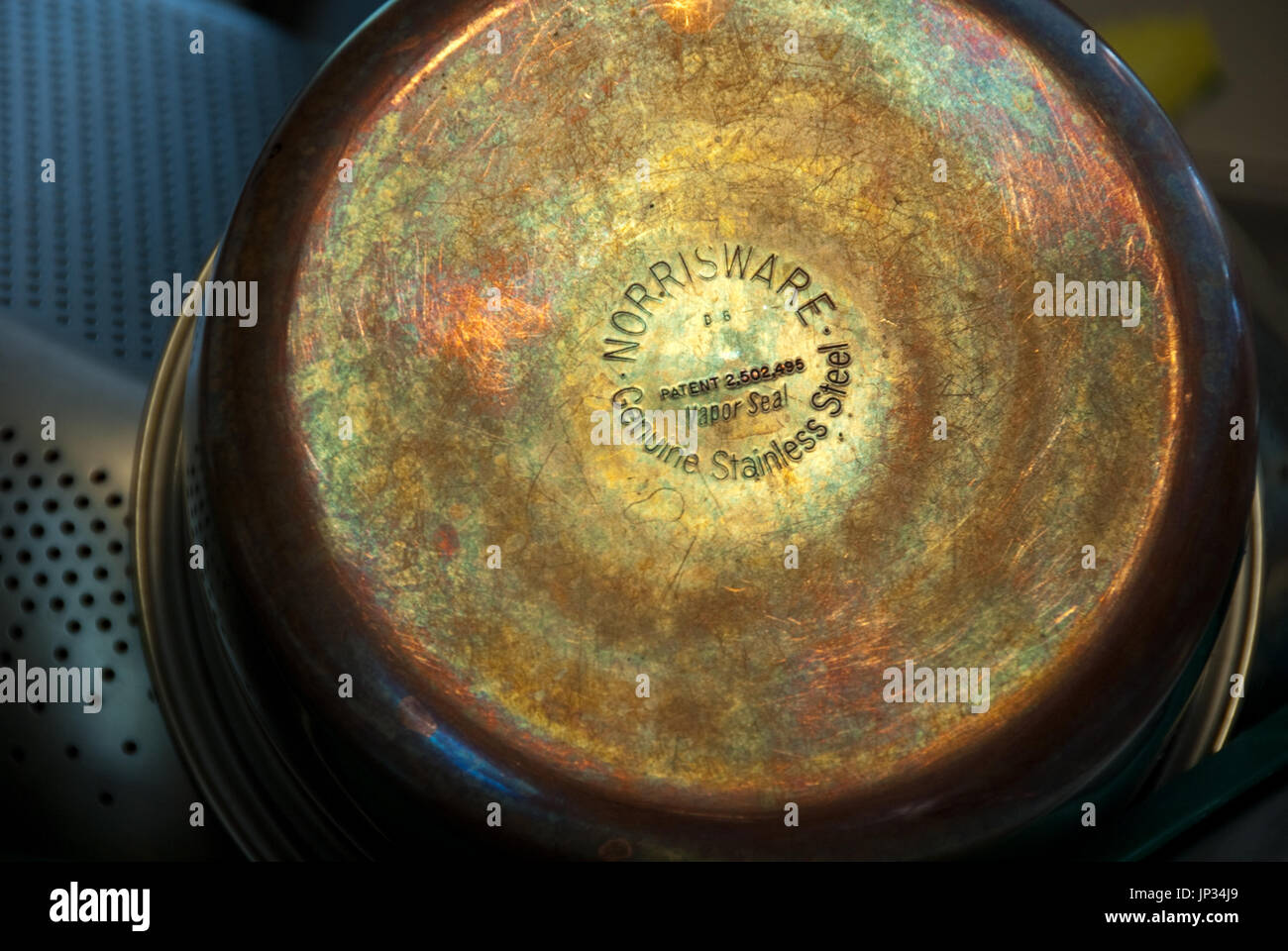 Reflecting light reveals the beautifully colored patina of copper bottom cookware. - Stock Image
