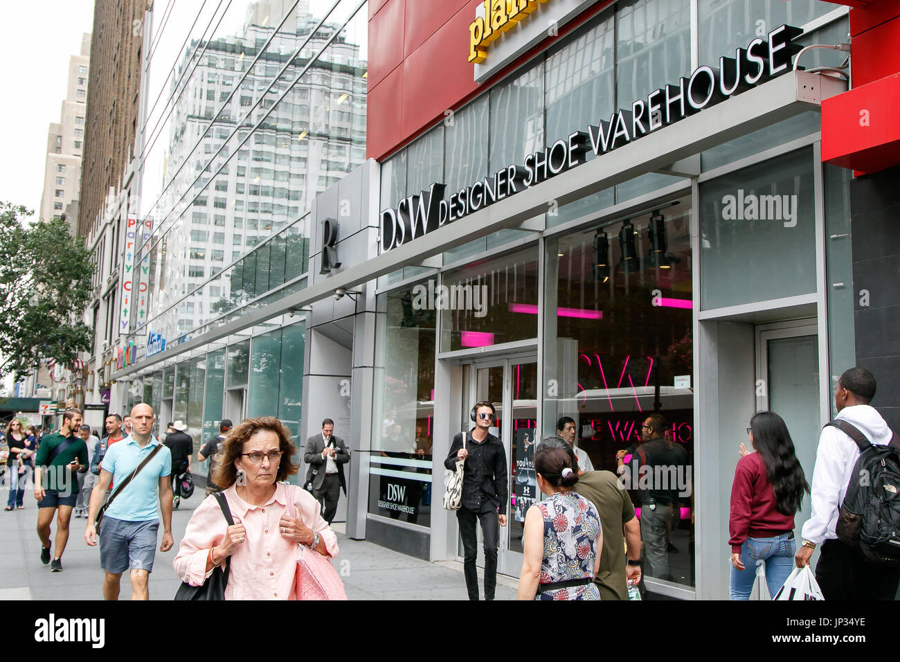 People walk by a DSW store in Manhattan. - Stock Image
