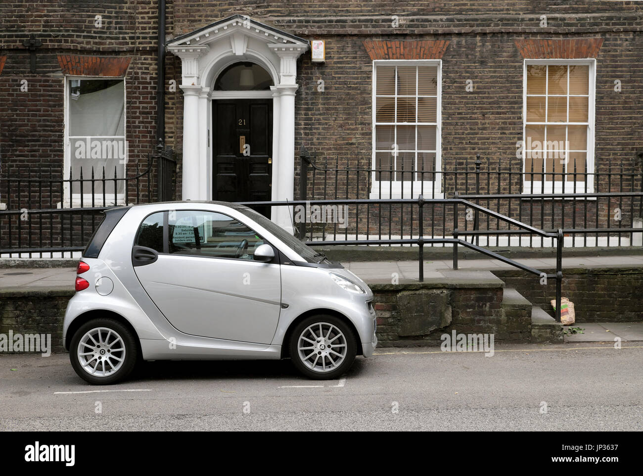 Silver fuel efficient Smart Car parked outside a Georgian house in London N1 UK   KATHY DEWITT - Stock Image