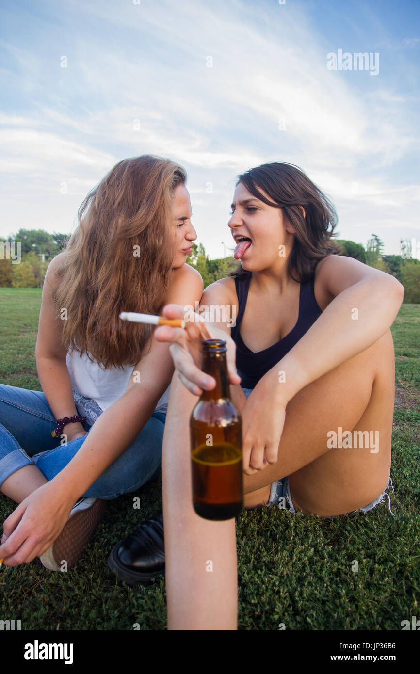 Two girls, friends, smoking cigarettes and drinking beer bottles in the park on a cloudy day. They are of celebration Stock Photo