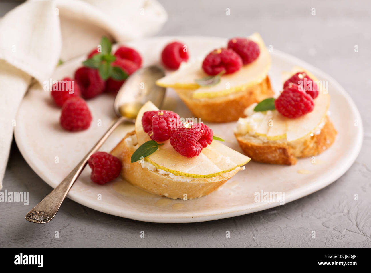 Open faced sandwiches with cheese, fresh pears and raspberry - Stock Image
