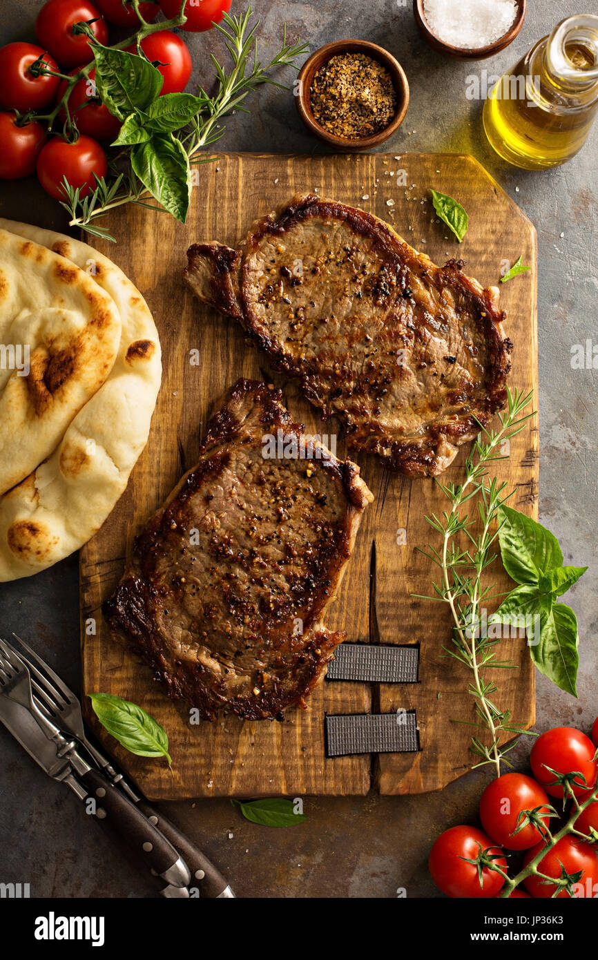 Grilled ribeye steaks with herbs and spices on a wooden board Stock Photo