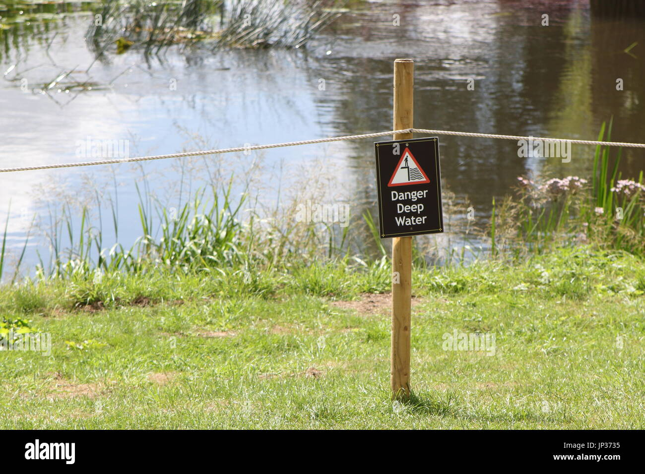 "Notice on a post in front of a roped off river or lake saying ""Danger Deep Water"" Stock Photo"