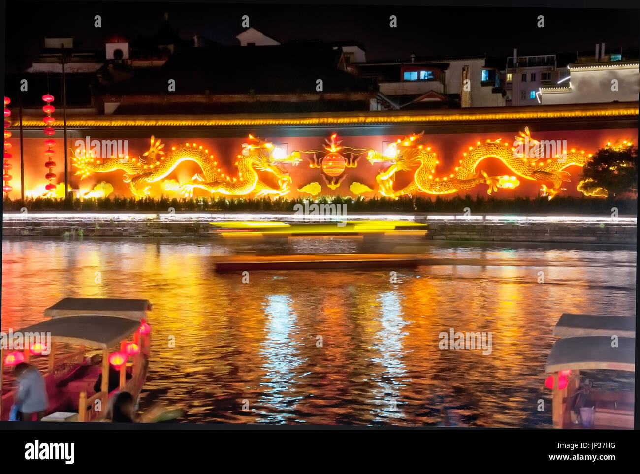 Golden dragons on a wall lit up at night within the city of Nanjing on a sunny winter day in the Qinhuai River scenic area in Jiangsu province China. - Stock Image