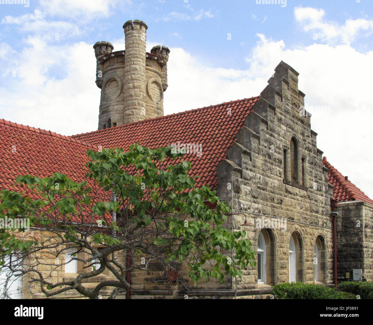 The old Santa Fe train depot in Shawnee Oklahoma is now a museum.  The building has an interesting stone tower.  This view is from the side. - Stock Image